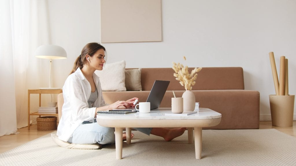 A woman doing research on her laptop on buying a home out of state