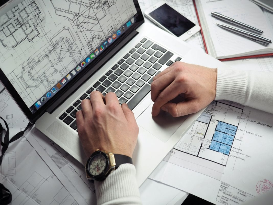 A person looking at a house plan on a laptop