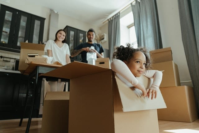 A family with large boxes and a little girl playing in one of them