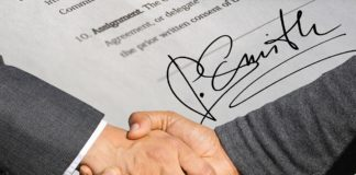 A signature on a contract and two people shaking hands.