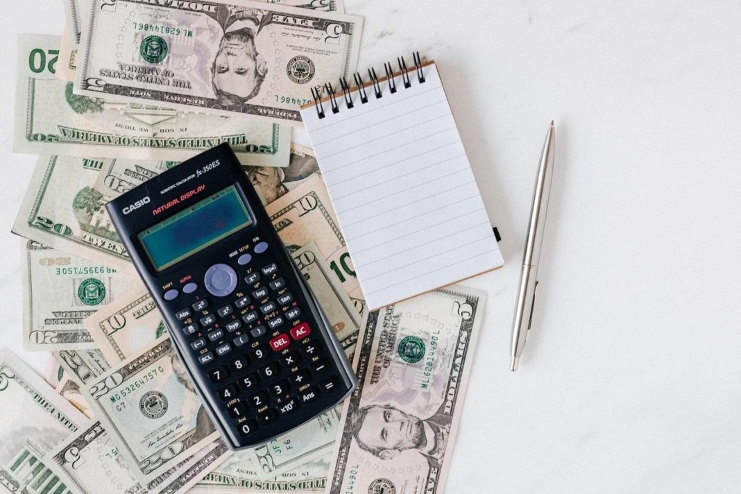 caclulator with dollars, notepad and pen